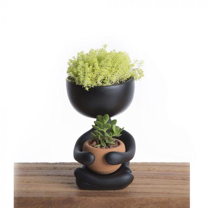 Maceta negra en forma de persona con plantas