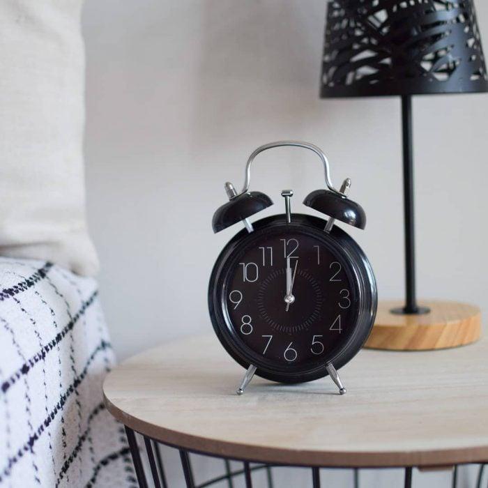 Reloj despertados negro sobre mesita de noche