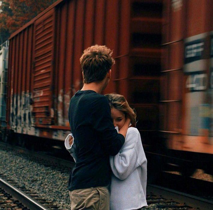 Pareja abrazándose mientras pasa el tren