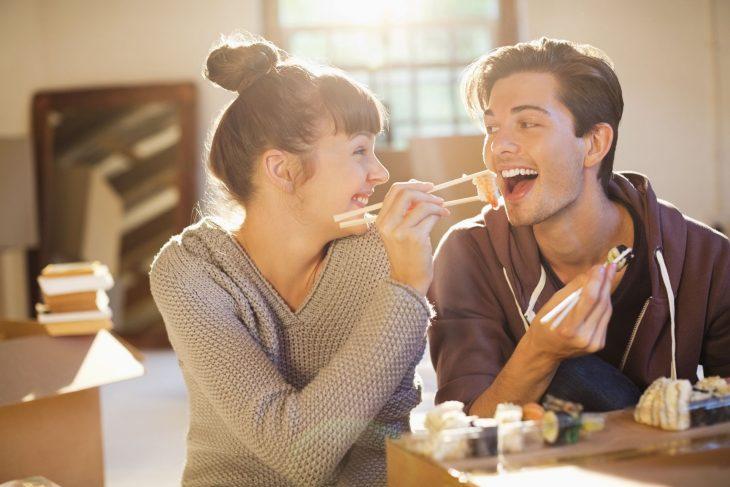 Mujer compartiéndole de su comida a su pareja