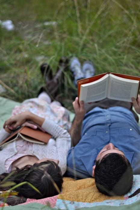 Pareja leyendo en el pasto