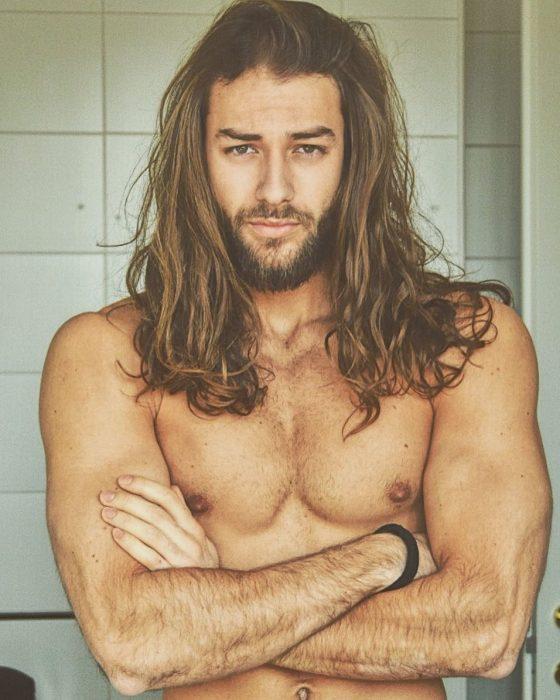 Hombre guapo de cabello largo y barba posando para foto