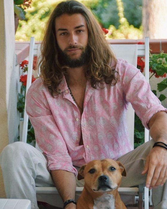 Hombre de cabello largo y barba posando junto a su perro