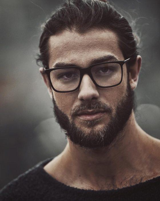 Hombre modelo con lentes y barba posando