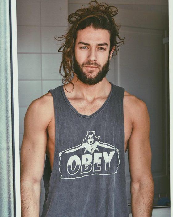 Hombre de cabello largo y barba posando para foto