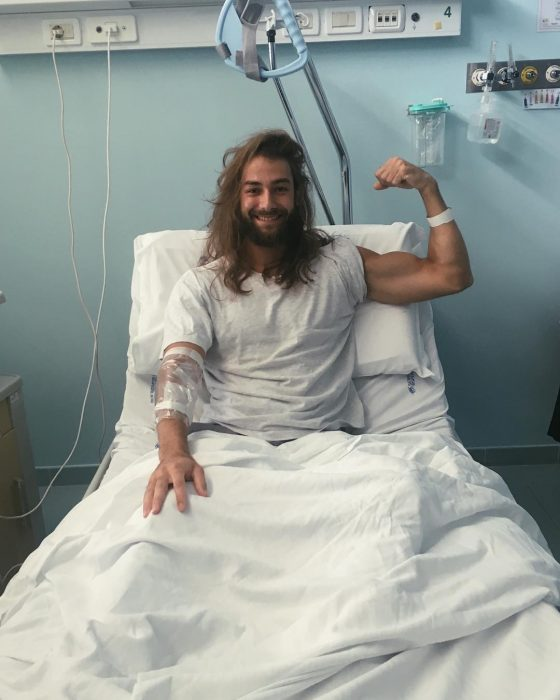 Hombre de cabello largo y barba en una cama de hospital