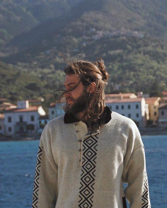 Hombre de cabello largo posando junto al mar