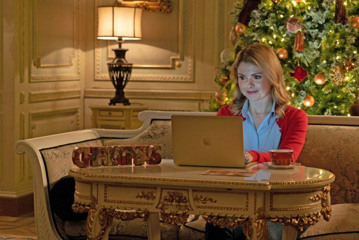 mujer rubia con computadora y árbol de navidad