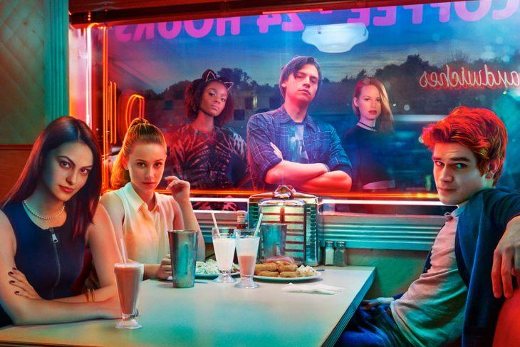 Grupo de chicos reunidos en una cafetería con luces neón