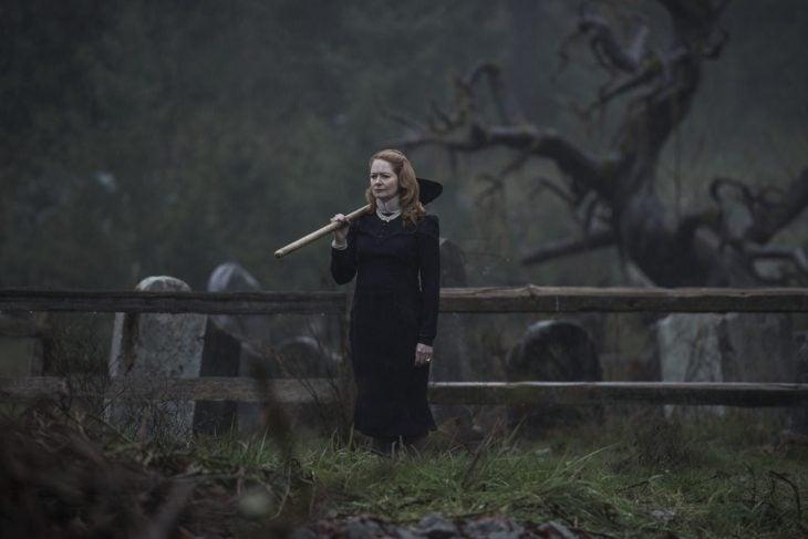 Mujer parada en un cementerio con rostro serio y una pala