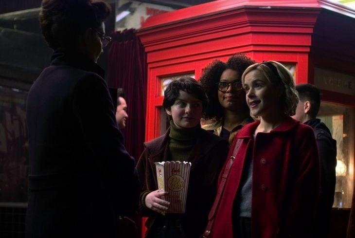 Tres amigas felices saliendo del cine y hablando con una mujer adulta