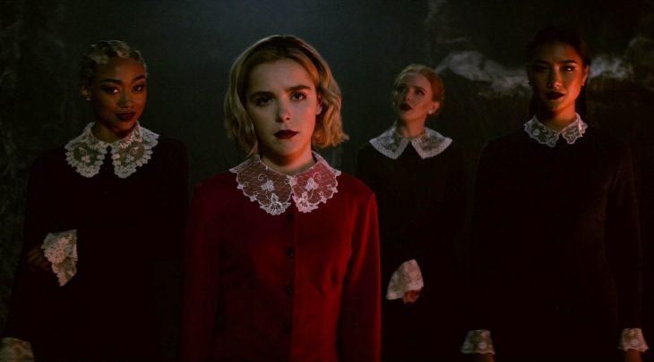 Grupo de mujeres reunidas en la oscuridad con semblantes intimidantes