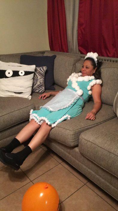 Mujer sentada en un sofá vestida como excelsa de la familia P. Luche