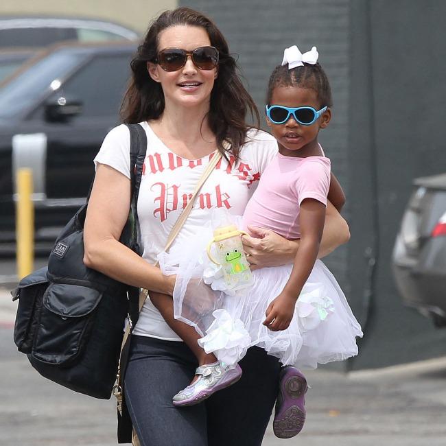 mamá cargando a su hija en brazos mientras pasean