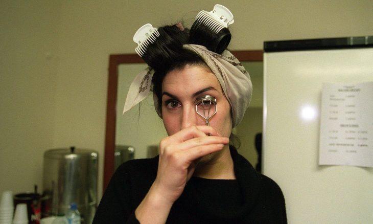 Amy Winehouse maquillándose tras bambalinas antes de un concierto en 2003
