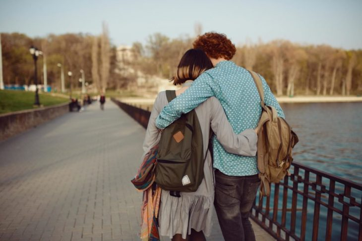 Pareja de enamorados camina abrazada