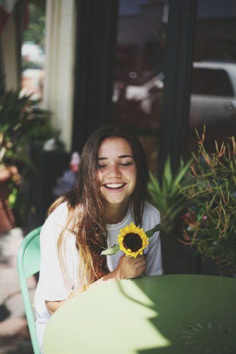 Chica riendo mientras sostiene un girasol