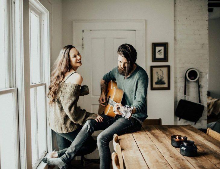 Novio toca la guitarra mientras novia sonrie feliz