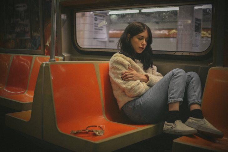 Mujer con semblante triste en un asiento del metro