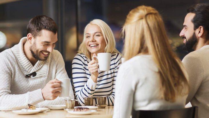 Mujeres y hombres riendo mientras beben café