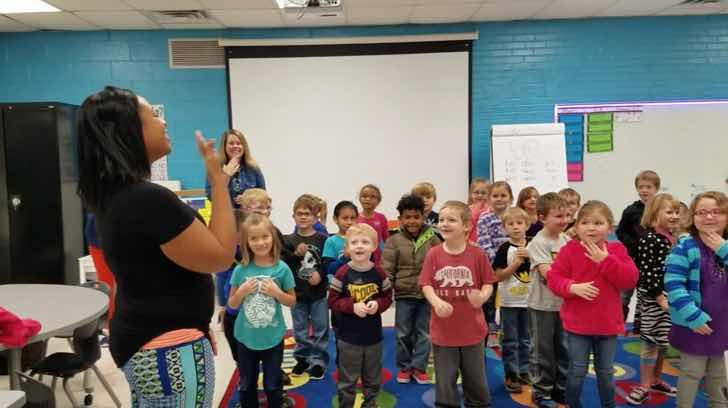 grupo de niños de preescolar cantando en lenguaje a señas