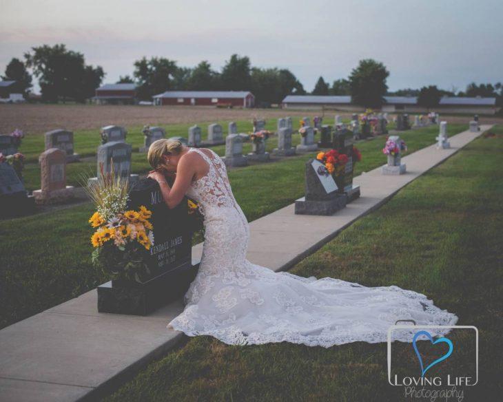 Chica vestida de novia llorando frente a la tumba de su prometido