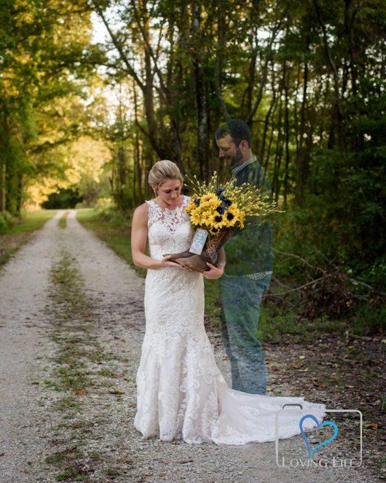 Chica sosteniendo un ramod e girasoles dentro de una bota mientras recuerda a su prometido fallecido