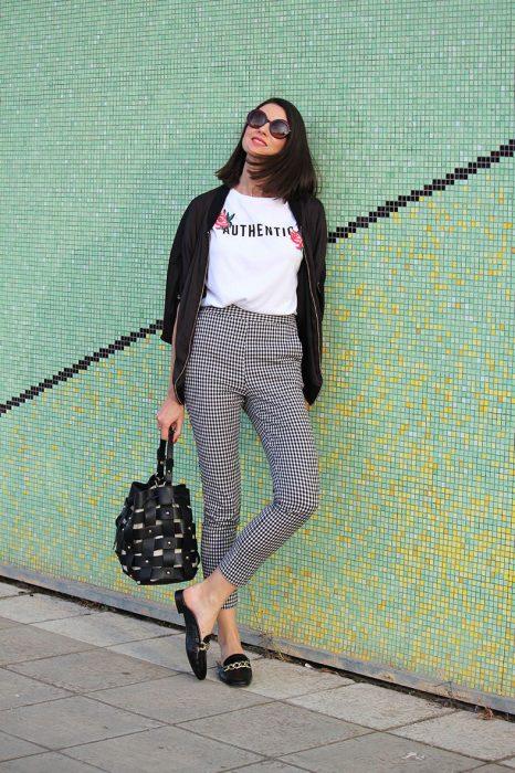 Chica usando un pantalón a cuadros y una chaqueta negra