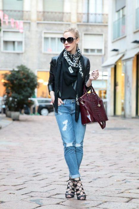 Chica usando jeans blazer negro, bufanda y bolso morado