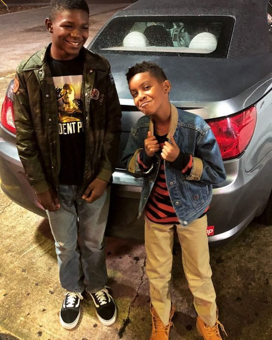 Chico y su acosador parados frente a un auto sonriendo para una fotografía