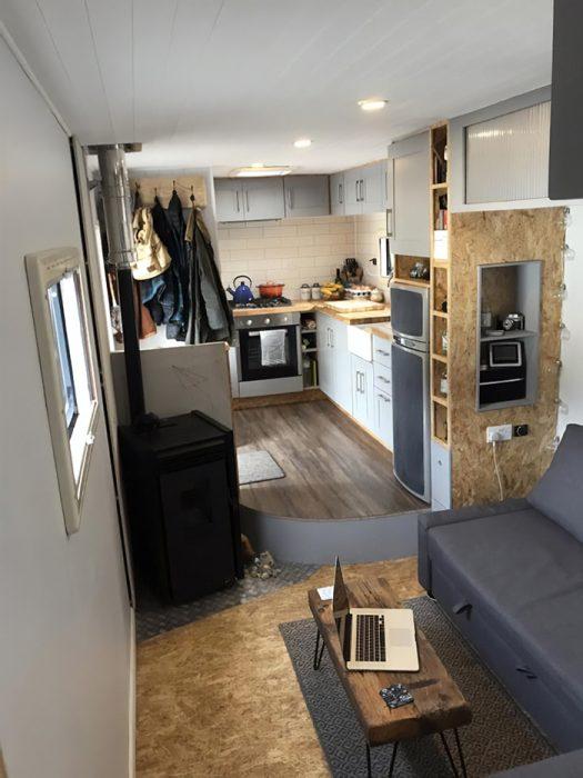 camión remodelado para convertirse en una casa con sillones cocina y comedor
