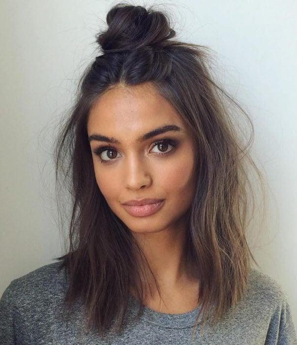 Chica de cabello corto con un chongo alto