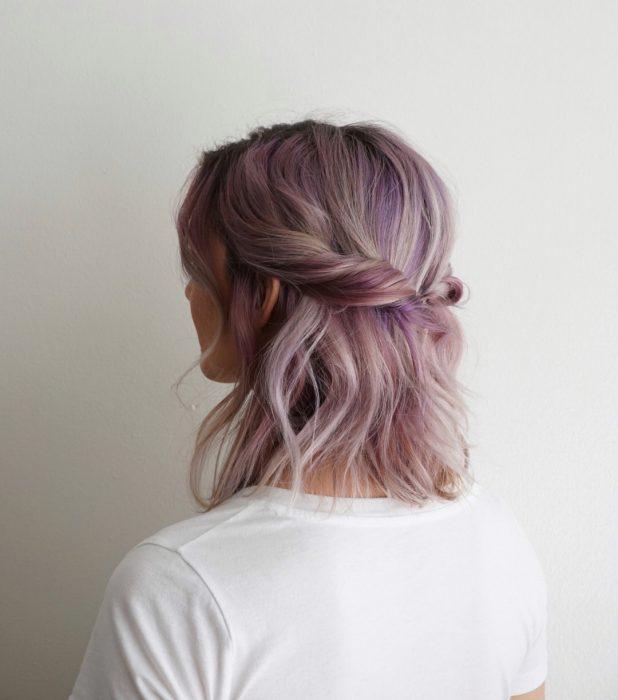 Chica de cabello corto y rosa recogido en una media cola