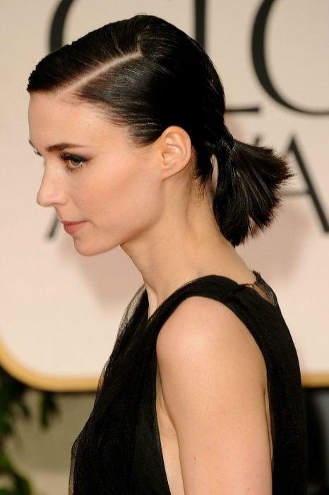 Chica con el cabello corto recogido en una coleta baja