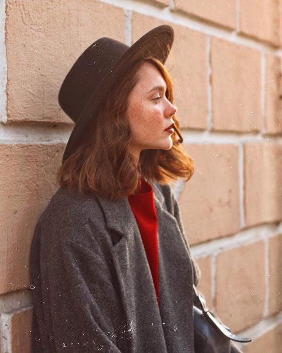 Chica con el cabello corto suelto y un sombrero