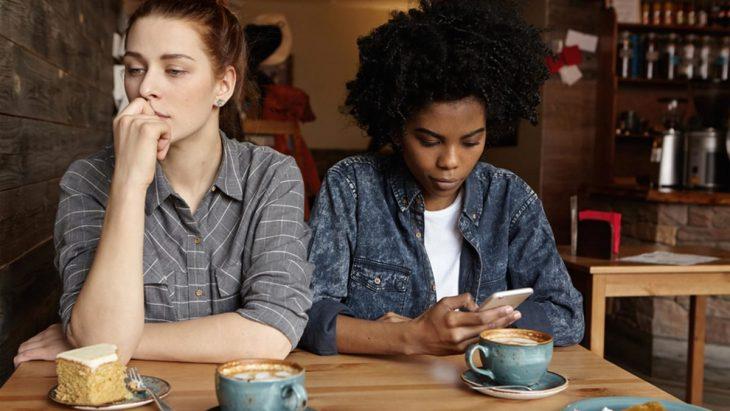 Amigas revisando su celular durante una salida al café