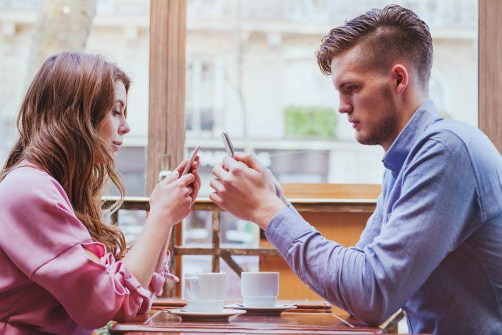 Pareja revisando su celular durante una cita