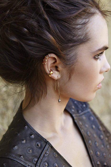 Chica con múltiples piercings en la oreja y chaqueta de cuero