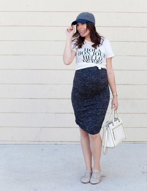 Chica embarazada usando una falda con camisa blanca