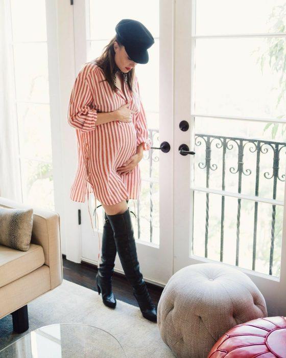 Chica embarazada usando un vestido a rajas de color naranja