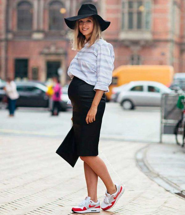 Chica embarazada usando un vestido y bluson blanco