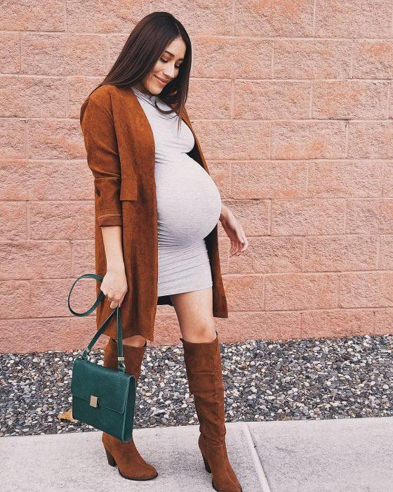 Chica embarazada usando un vestido de color gris con botas café