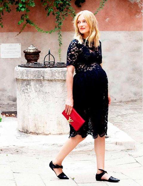 Chica embarazada usando un vestido de color negro