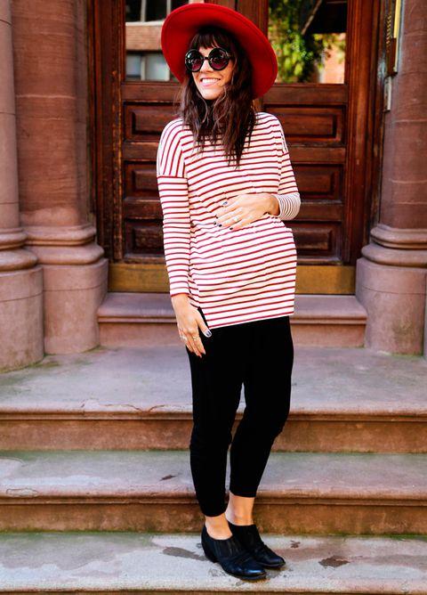 Chica embarazada usando una camisa grande de color naranaja