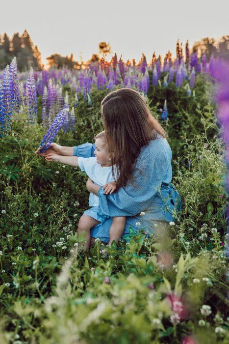 mamá e hijo jugando con flores en el campo