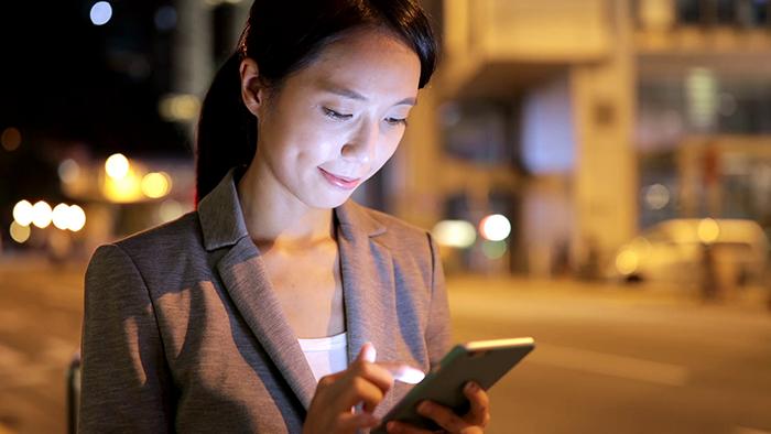 mujer con celular prendido y luz