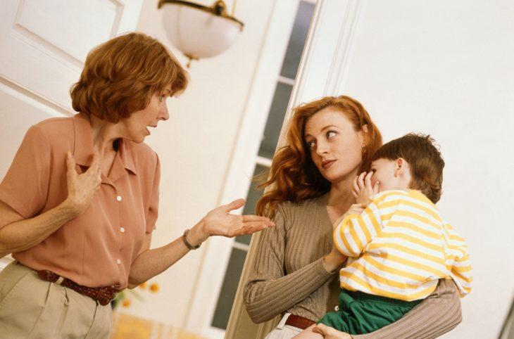 Relación conflictiva con la suegra; mujer mayor mirando a su nuera; chica pelirroja cargando a su bebé