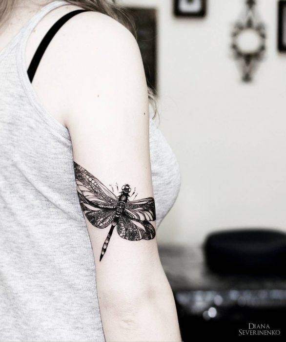 Tatuaje de libélula en el brazo