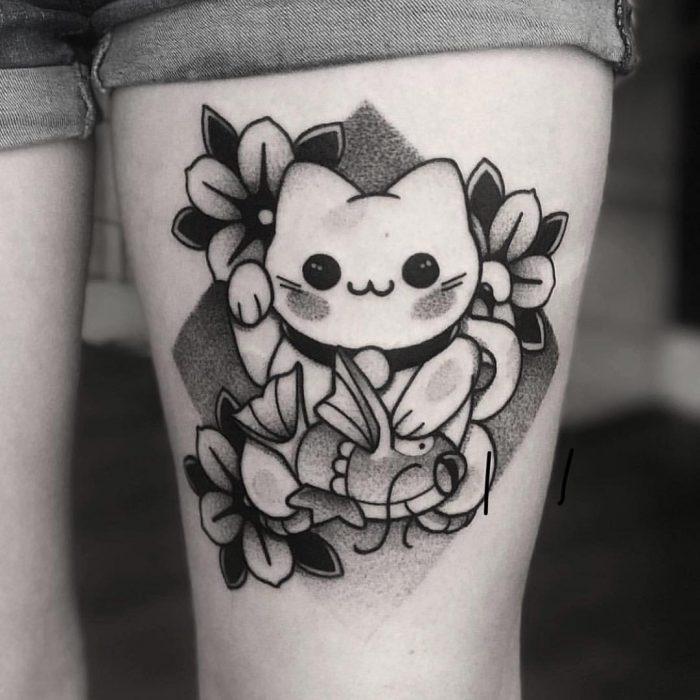 Tatuaje de gato maneki en la pierna