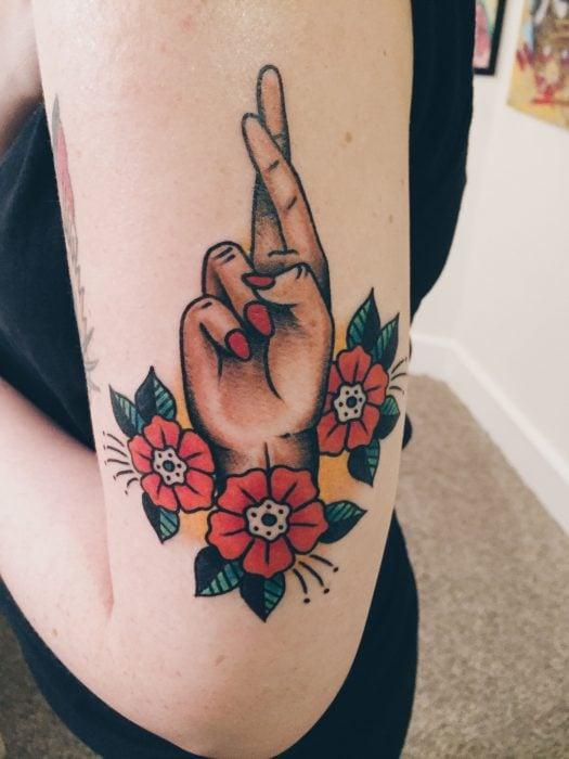 Tatuaje de mano cruzando los dedos en el brazo